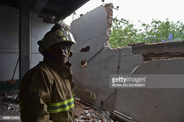 A firefighter works to demolish a damaged wall after a strong earthquake in Mexico City on May 8 2014 A strong 64magnitude earthquake rattled Mexico...