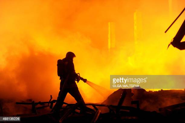 A firefighter works to extinguish a fire at a warehouse of car spare parts in St Petersburg on October 17 2015 AFP PHOTO / OLGA MALTSEVA