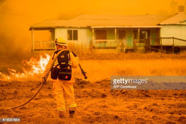 A firefighter works to protect a home in Mariposa California on July 19 2017 The Detwiler fire which has burned more than 45000 acres and destroyed...