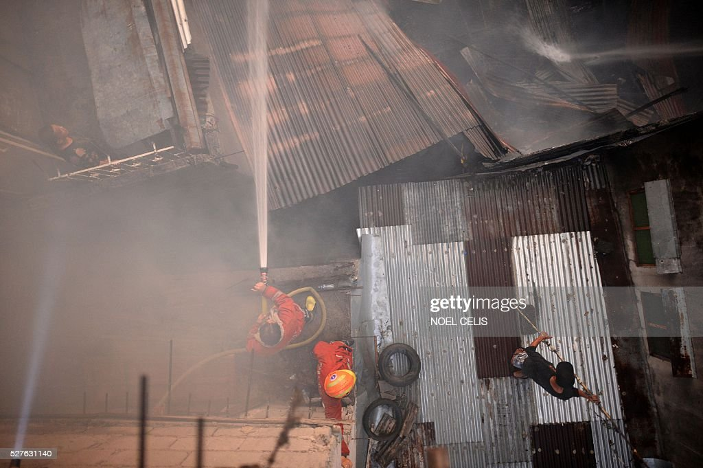 Firefighters and a resident try to put out a fire that swept over several houses in a residential area in Manila on May 3, 2016. No one was hurt in the fire, according to initial reports. / AFP / NOEL