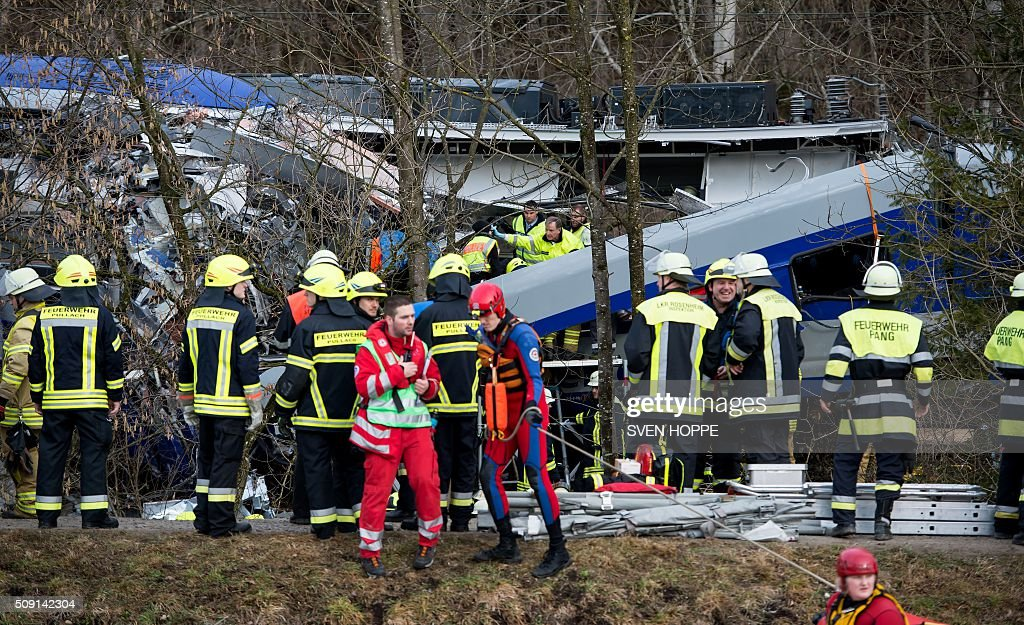 Firefighters and emergency doctors work at the site of a train accident near Bad Aibling, southern Germany, on February 9, 2016. Two Meridian commuter trains operated by Transdev collided near Bad Aibling, around 60 kilometres (40 miles) southeast of Munich, killing at least four people and injuring around 100, police said. The cause of the accident was not immediately clear. / AFP / dpa / Sven Hoppe / Germany OUT