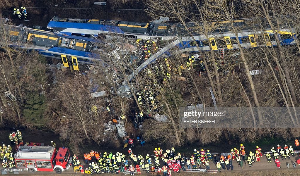 CROP - Firefighters and emergency doctors work at the site of a train accident near Bad Aibling, southern Germany, on February 9, 2016. Two Meridian commuter trains operated by Transdev collided head-on near Bad Aibling, around 60 kilometres (40 miles) southeast of Munich, killing at least eight people and injuring around 100, police said. The cause of the accident was not immediately clear. / AFP / dpa / Peter Kneffel / Germany OUT