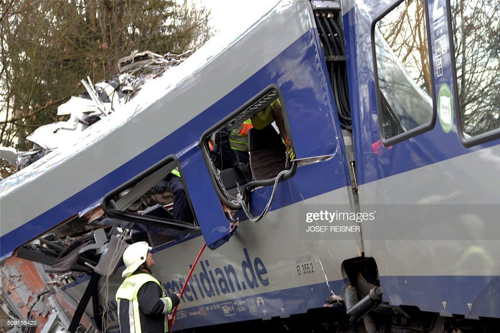 Firefighters and emergency doctors work at the site of a train accident near Bad Aibling, southern Germany, on February 9, 2016. Two Meridian commuter trains operated by Transdev collided head-on near Bad Aibling, around 60 kilometres (40 miles) southeast of Munich, killing at least eight people and injuring around 100, police said. The cause of the accident was not immediately clear. / AFP / dpa / Josef Reisner / Germany OUT
