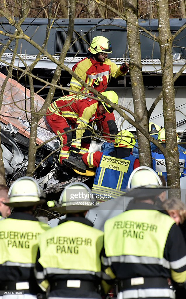 Firefighters and emergency doctors work at the site of a train accident near Bad Aibling, southern Germany, on February 9, 2016. Two commuter trains collided head-on near Bad Aibling, around 60 kilometres (40 miles) southeast of Munich, killing at least eight people and injuring around 100, in what is believed to be the country's first deadly rail accident in three years. / AFP / Lukas BARTH