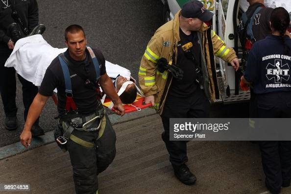 Firefighters and emergency personnel bring an injured man to an ambulance following the crash of the Staten Island Ferry into a dock in the city's...