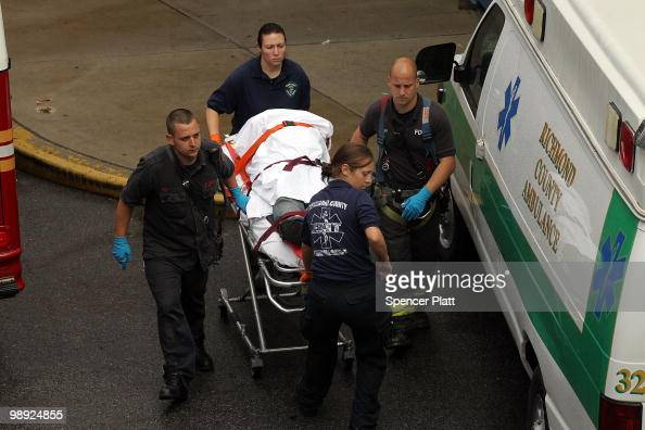 Firefighters and emergency personnel bring an injured person to an ambulance following the crash of the Staten Island Ferry into a dock in the city's...