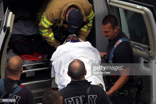 Firefighters and emergency personnel place an injured man in an ambulance following the crash of the Staten Island Ferry into a dock in the city's...