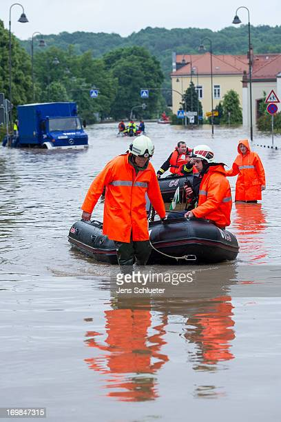 Firefighters and helpers evacuate inhabitants in the flooded city center on June 3 2013 in Grimma Germany Heavy rains are pounding southern and...