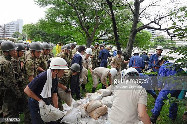Firefighters and Japan Ground SelfDefense Force members sandbag at the bank of swollen Shirakawa River on July 12 2012 in Kumamoto Japan 19 people...