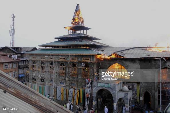 Firefighters and locals try to douse a Sufi shrine that is engulfed in flames on June 25 2012 in Srinagar the summer capital of Indian administered...