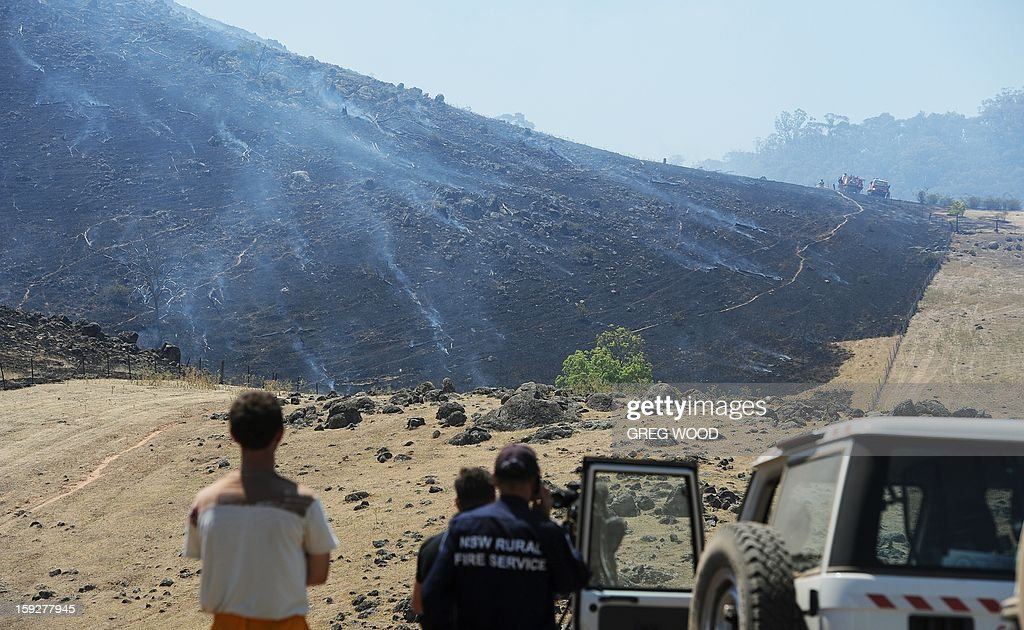 Firefighters and media look on as a scrubfire burns up a hillside south of Bookham, near Yass in the southern region of Australia's New South Wales state, on January 11, 2013. After two days of cooler weather, heat and high winds returned to much of the country as fire crews tackled the infernos that have been burning for a week, 18 of them out of control in the most populous state of New South Wales. AFP PHOTO / Greg WOOD