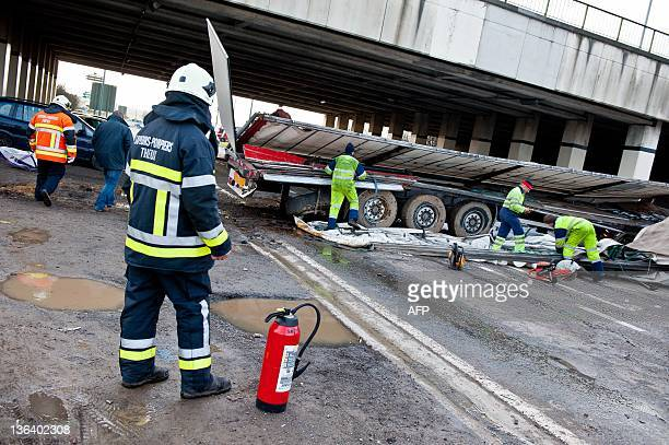 Firefighters and members of a repair service work after a lorry drove off a bridge on the E25 highway and crashed into the N678 road below in...