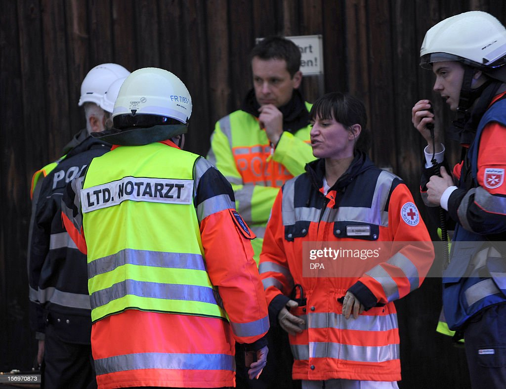 Firefighters and members of the medical services talk at the scene of a fire at a house with a workshop for handicapped people in Titisee- Neustadt, southern Germany on November 26, 2012. Fourteen people died after a fire broke out.