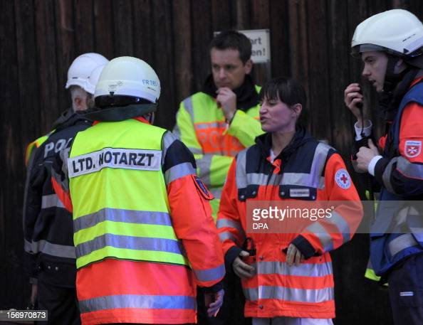 Firefighters and members of the medical services talk at the scene of a fire at a house with a workshop for handicapped people in Titisee Neustadt...