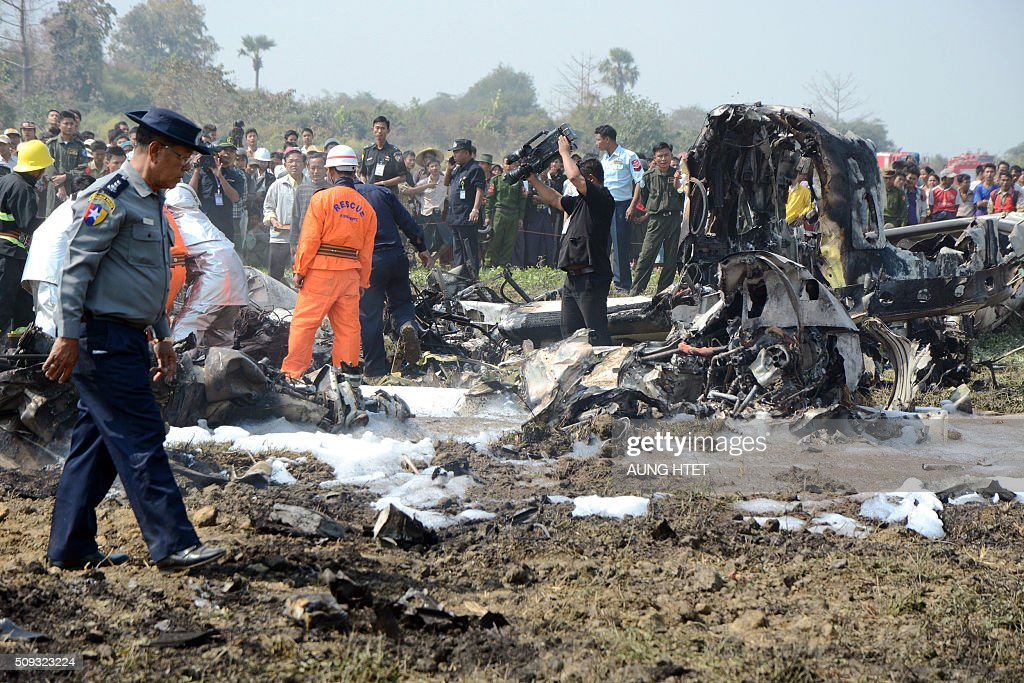 Firefighters and officials inspect the wreckage of a military passenger plane which crashed in a field near the airport in the capital of Naypyidaw on February 10, 2016. Four Myanmar military personnel were killed and one was seriously injured after the small air force propeller plane crashed shortly after take off in the capital Naypyidaw, officials said. AFP PHOTO / AUNG HTET / AFP / Aung Htet