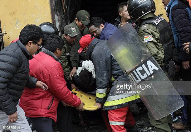 Firefighters and police carry a victim out of the City Hall in El Alto Bolivia on February 17 2016 Six people died from smoke inhalation when a crowd...