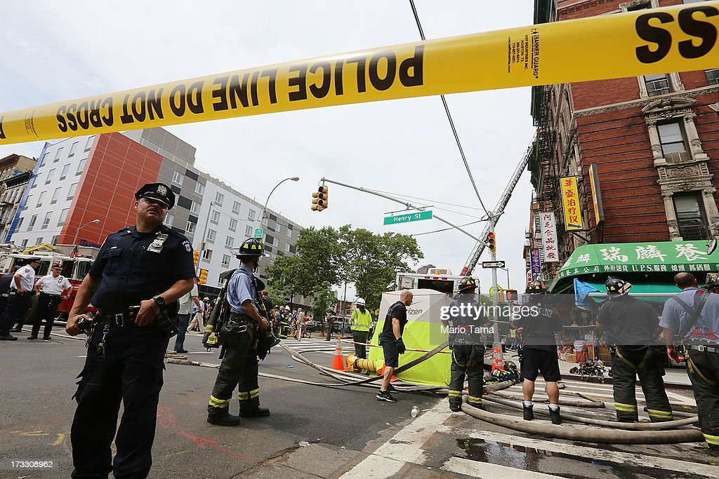 Firefighters and police gather at the scene of an explosion and partial building collapse in the Chinatown neighborhood on July 11, 2013 in New York City. Seven people were injured in the apparent basement gas explosion in the five-story building in Lower Manhattan.