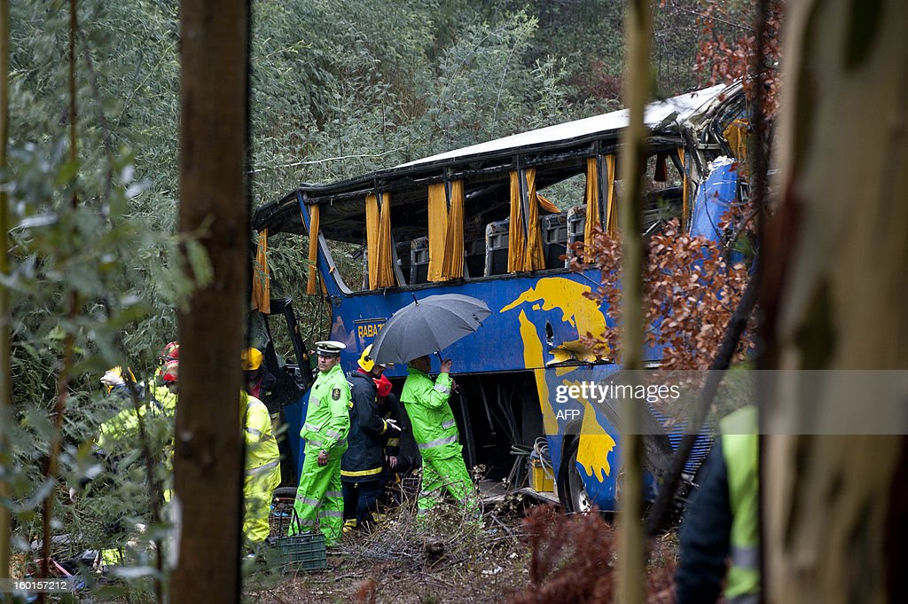 Firefighters and police officers stand next to a bus which crashed on the IC8 road near Carvalhal, in the central Castelo Branco district, on January 27, 2013. Ten people were killed and 33 were hurt when a coach slid off a rain-soaked road and plunged into a ravine in central Portugal today, rescue services said. More than 250 firefighters, 88 emergency vehicles and a helicopter were deployed to the scene.