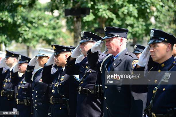 Firefighters and police salute during the playing of Taps at the at the 9/11 Memorial during ceremonies for the twelfth anniversary of the terrorist...