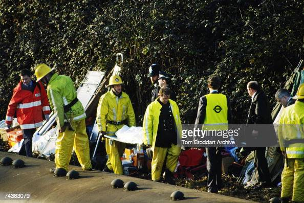 Firefighters and policemen carry away the dead and injured after a rail crash near Clapham Junction in London in which 35 people were killed and over...