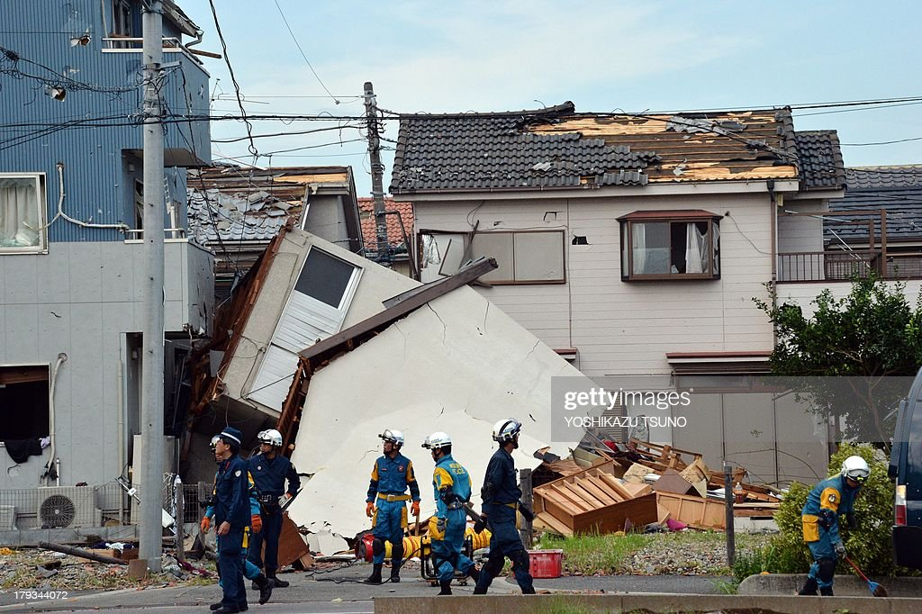 Firefighters and policemen check damaged houses after a tornado tore though Koshigaya in Saitama prefecture, suburban Tokyo on September 2, 2013. Several dozen people were injured when a tornado ripped through parts of eastern Japan, tearing off roofs and uprooting buildings. AFP PHOTO / Yoshikazu TSUNO