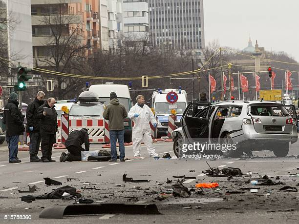 Firefighters and policemen remove the wrecked car on a road at Bismarck Street in the Charlottenburg neighborhood after it exploded in Berlin Germany...