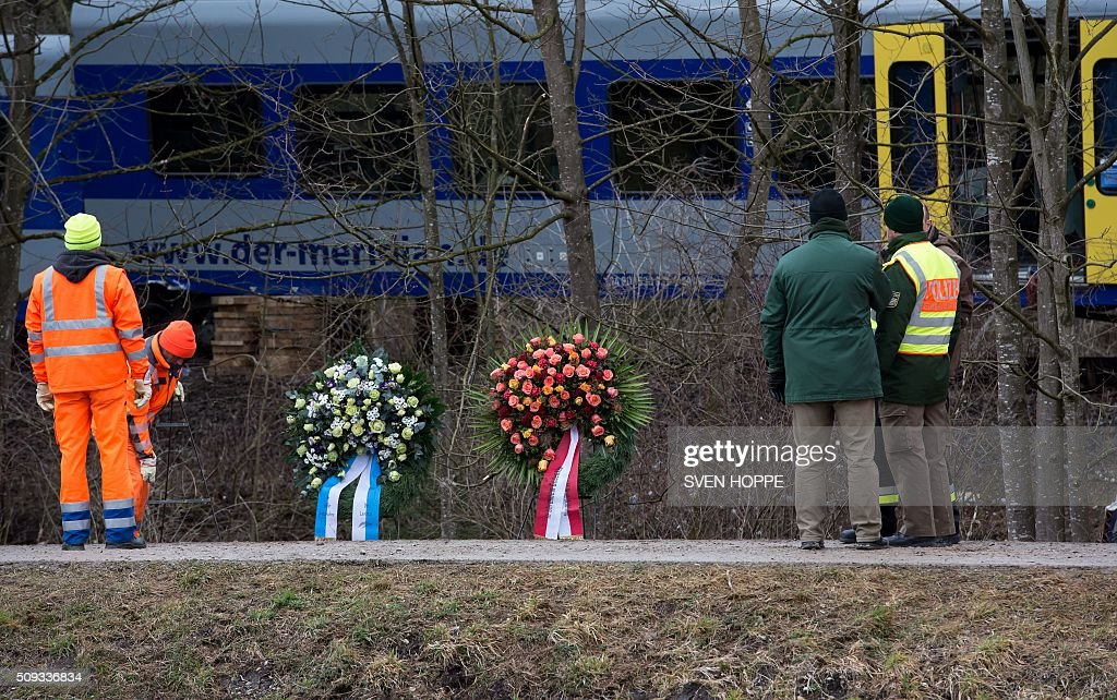 Firefighters and policemen stand in front of wreaths laid down at the site of a train accident near Bad Aibling, southern Germany, on February 10, 2016. Two Meridian commuter trains operated by Transdev on February 9, 2016 collided head-on near Bad Aibling, around 60 kilometres (40 miles) southeast of Munich, killing ten people and injuring around 80, police said. / AFP / dpa / Sven Hoppe / Germany OUT