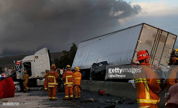 Firefighters and rescue personnel are on scene after a big rig crashed through the center divider crushing a car underneath and causing four other...