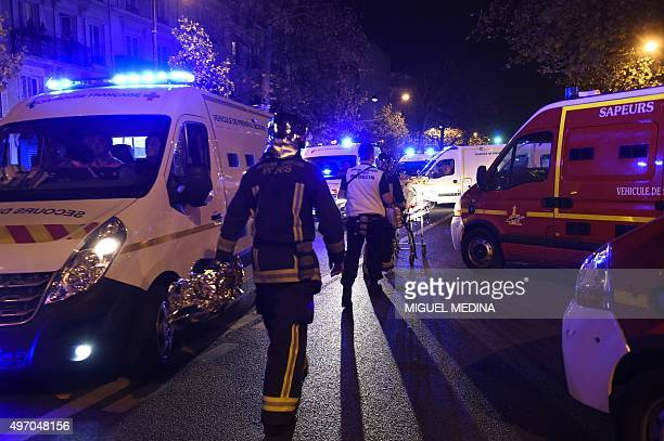 Firefighters and rescuers evacuate injured people on Boulevard des Filles du Calvaire close to the Bataclan concert hall in central Paris early on...