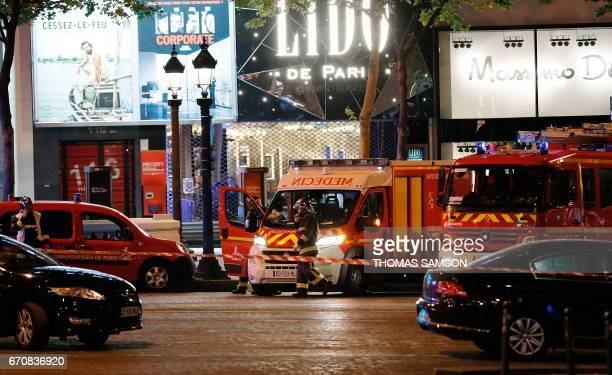 Firefighters and rescuers stand by the site of a shooting on the Champs Elysees in Paris on April 20 2017 One police officer was killed and another...