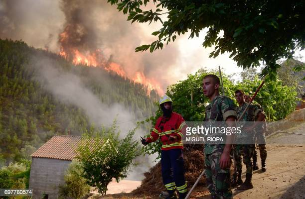 Firefighters and soldiers work to extinguish a wildfire in Carvalho next to Pampilhosa da Serra on June 19 2017 More than 1000 firefighters are still...