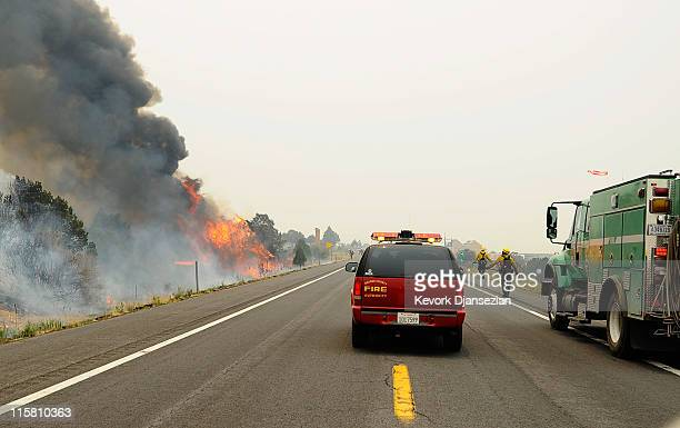 Firefighters and vehicles line the opposite side of the road after setting a backburn on Highway 191 in an attempt to control a raging wildfire on...