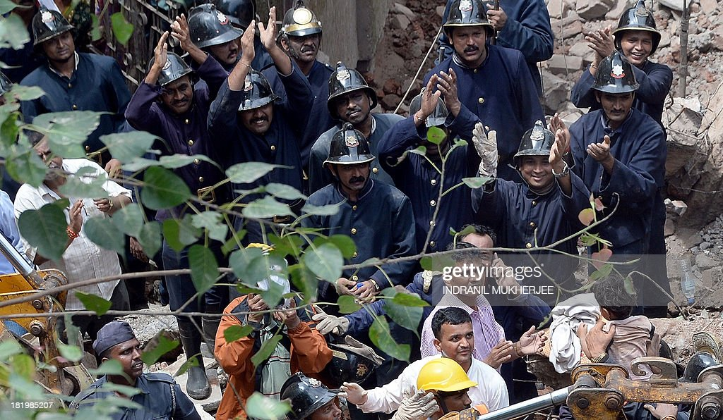 Firefighters applaud as a child (bottom R) is brought out alive from the rubble of a building collapse in Mumbai on September 27, 2013. A five-storey residential block collapsed in Mumbai at daybreak killing at least three people and leaving up to 70 feared trapped inside, in the latest building disaster to hit India's financial capital. AFP PHOTO/Indranil MUKHERJEE