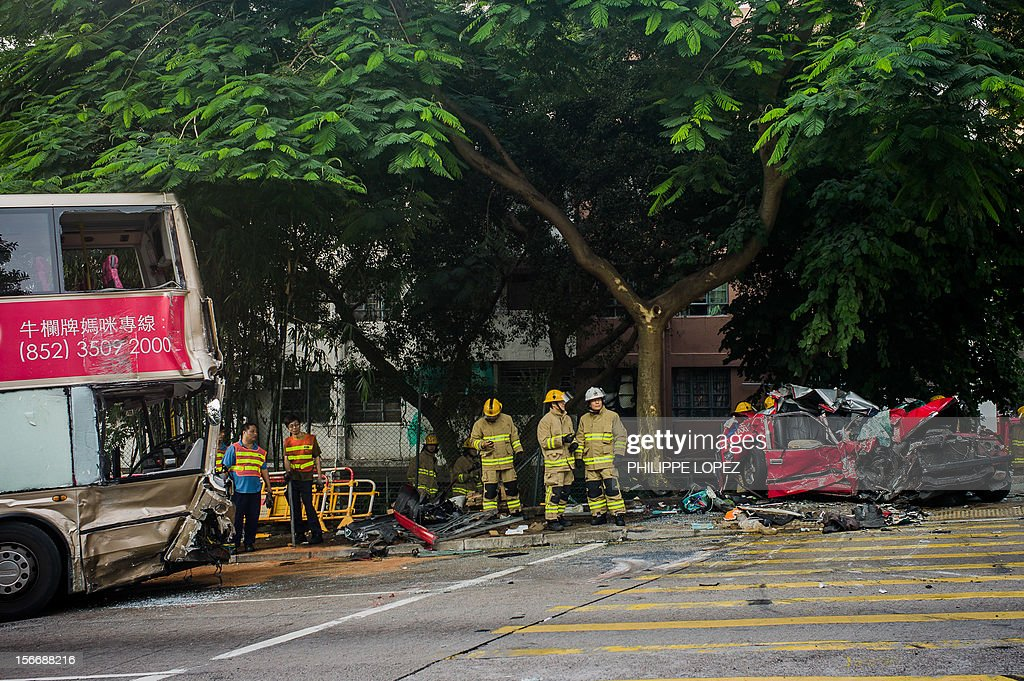 Firefighters are seen next to a taxi crushed during an accident with two double-decker buses in Hong Kong on November 19, 2012. Three people died and about 50 were injured in the crash which occured in the eastern district of Shau Kei Wan. AFP PHOTO / Philippe Lopez