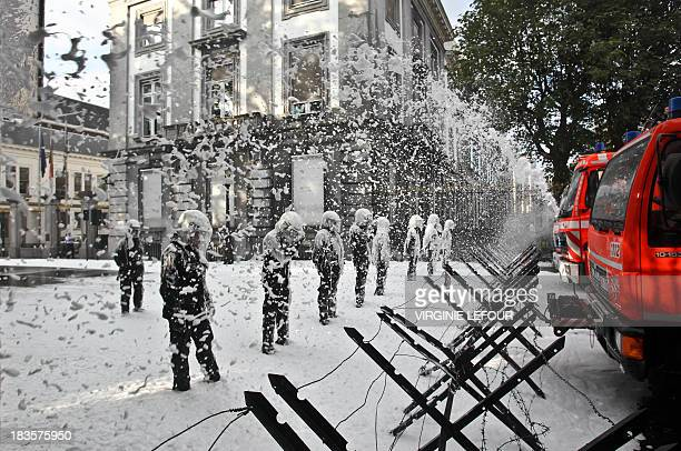 Firefighters are spraying foam to police from behind the barricades during a protest on October 7 2013 near the Lambermont in Brussels the residence...
