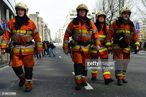 Firefighters arrive at a security perimeter set near Maalbeek Maelbeek metro station on March 22 2016 in Brussels after a blast at this station near...