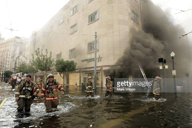 Firefighters arrive at a store on fire on Canal Street August 31 2005 in New Orleans Louisiana Devastation is widespread throughout the city with...