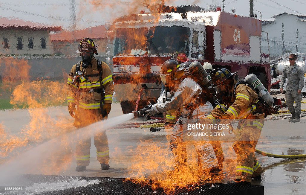 Firefighters attempt to extinguish a fire during a training session at Palmerola US military base, 80 kms north of Tegucigalpa, on May 8, 2013. Firefighters from Honduras, Nicaragua, Panama, Guatemala, Belize and El Salvador received specialized training from US firefighters. AFP PHOTO/Orlando SIERRA