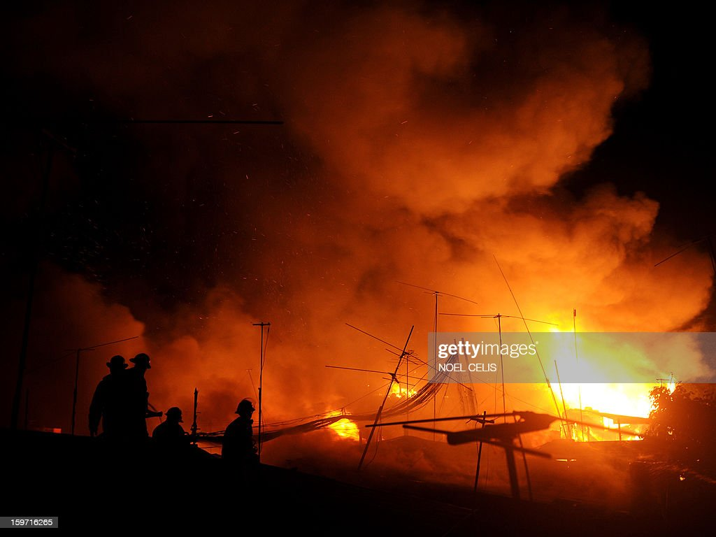 Firefighters attempt to extinguish a fire that engulfed a residential area in Manila on January 19, 2013. Almost 50 houses were destroyed leaving a hundred families homeless, according to local media reports.