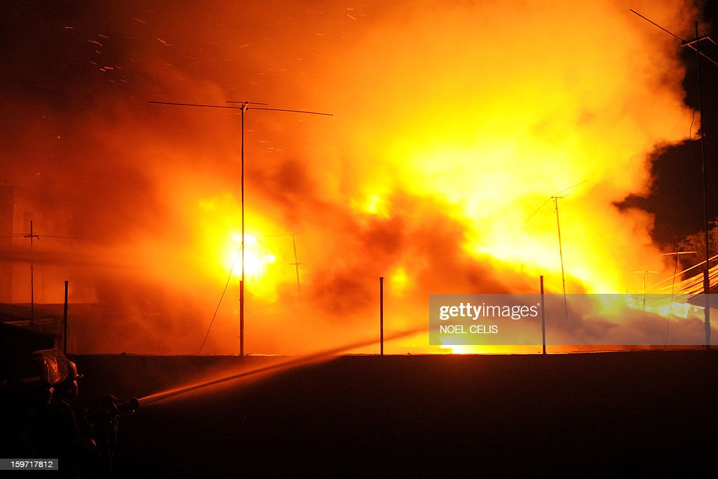 Firefighters attempt to extinguish a fire that engulfed a residential area in Manila on January 19, 2013. Almost 50 houses were destroyed leaving a hundred families homeless, according to local media reports. AFP PHOTO/NOEL CELIS