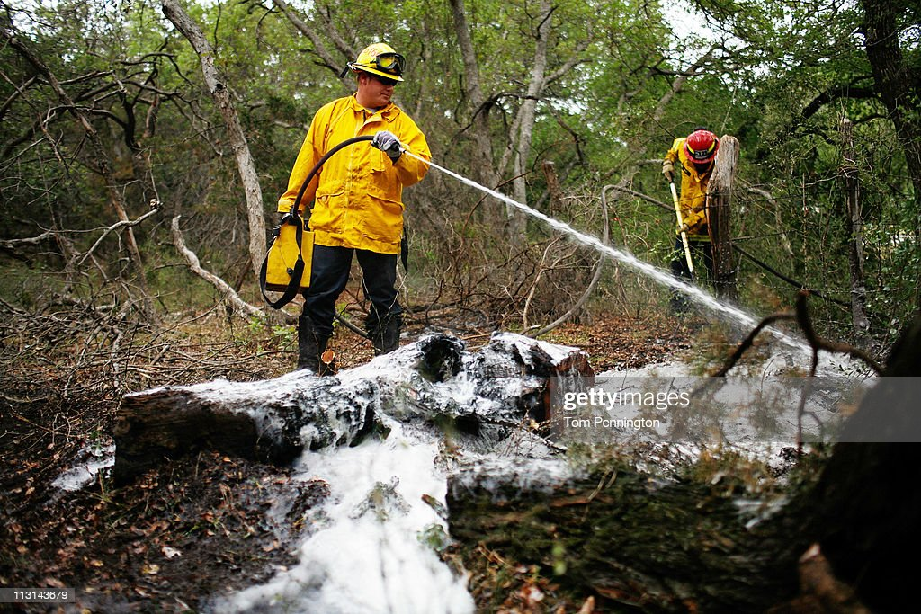 Firefighters Austin McKitrick (L) and Captain Wade West work to extinguish a hotspot fire in rugged terrain April 24, 2011 near Graford, Texas. Cooler tempratures and high humidity has helped firefighters contain the PK Complex Fire that has destroyed more than 160 homes in the area.