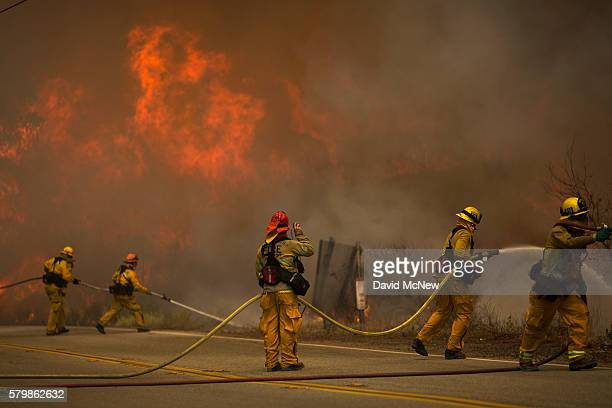 Firefighters battle flames in Placerita Canyon at the Sand Fire on July 24 2016 in Santa Clarita California Tripledigit temperatures and dry...