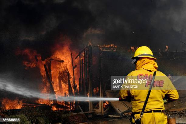 Firefighters battle strong winds as they try to save a house during the Thomas wildfire in Ventura California on December 5 2017 Firefighters battled...