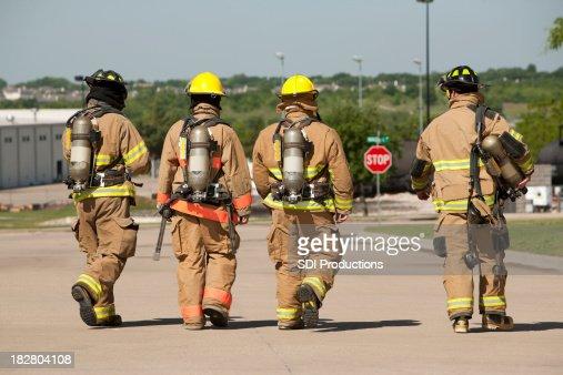 Feuerwehrleute hinter zu Fuß entfernt von Feuer