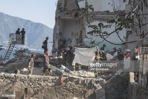 Firefighters block the view with sheets as they extract a body from the debris of a collapsed building after two floors collapsed in a small...