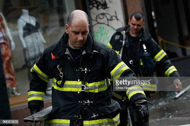 Firefighters carry a ladder away from the scene of a threealarm fire that broke out at 502 East 14th Street across from Stuyvesant Town in lower...