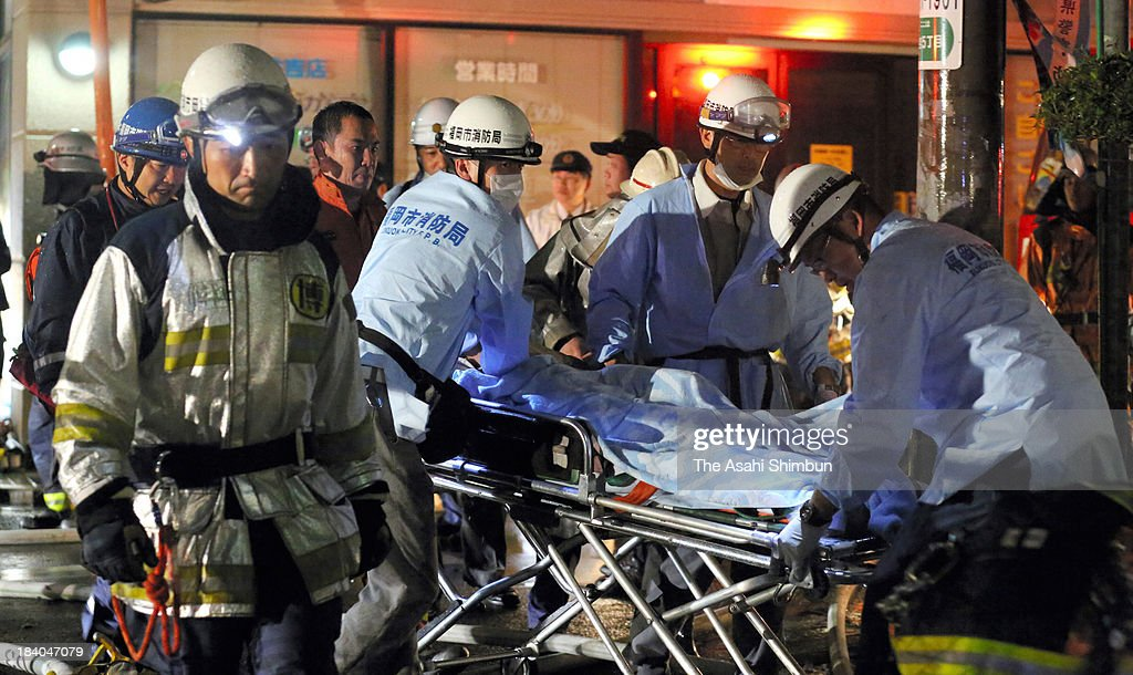 Firefighters carry a patient on the stretcher from a hospital fire site on October 11, 2013 in Fukuoka, Japan. 2 staffs and 8 patients were confirmed dead.
