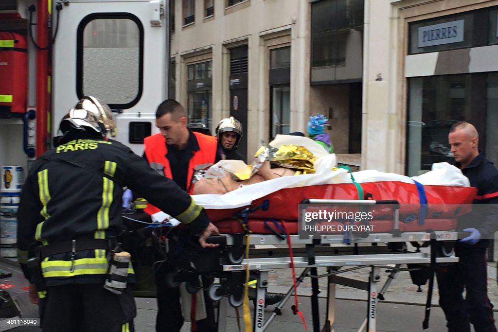 Firefighters carry an injured man on a stretcher in front of the offices of the French satirical newspaper Charlie Hebdo in Paris on January 7 after...