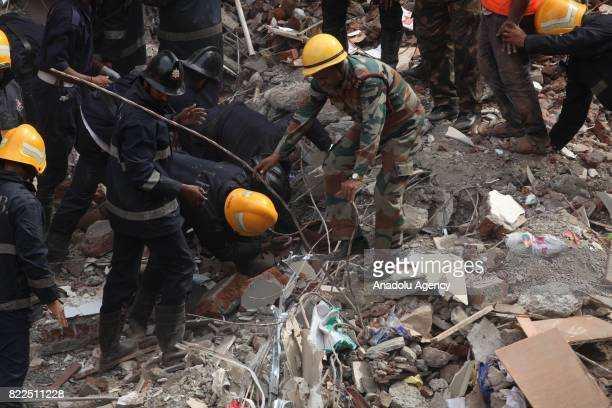 Firefighters carry out search and rescue work for the survivors in the debris at site of a collapsed building in Mumbai on July 25 2017 At least six...