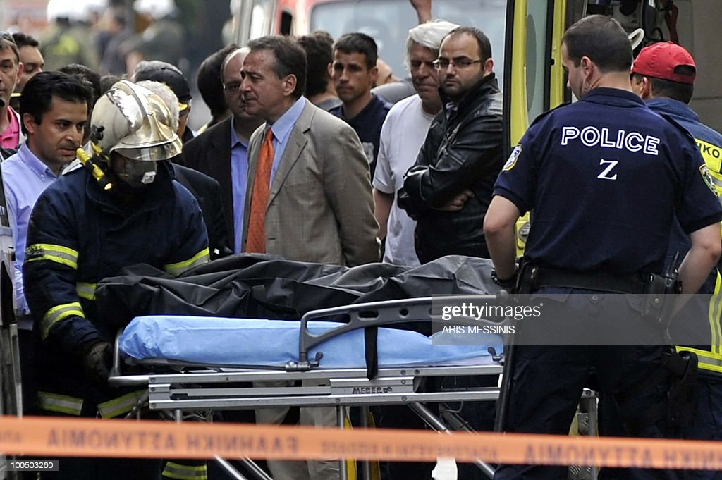 Firefighters carry the body of victim after a fire at an Athens bank branch during a demonstration in Athens on May 5, 2010. Athens police chiefs mobilized all their forces, including those not on active duty, to restore order on May 5 amid rioting during protests against a government austerity drive. Police were put on a 'general state of alert' to deal with the clashes after three people died in a bank that was firebombed on the margins of the demonstrations. AFP PHOTO / Aris Messinis